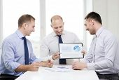 business and office concept - smiling businessman showing others charts in office