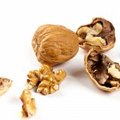 stock photo of walnut  - Walnut and a cracked walnuts isolated on the white background - JPG