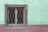 image of wainscoting  - An old window on a facade painted with unusual colors - JPG