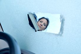 pic of scrape  - Woman scraping ice from a windshield - JPG