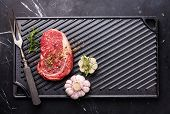 stock photo of ribeye steak  - Raw fresh Blank Angus Steak Ribeye on cast iron grill surface on marble background - JPG