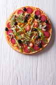 image of rocket salad  - Hot Italian pizza with rocket salad and salami vertical view from above - JPG