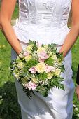 stock photo of ivory  - Bride holding her bridal bouquet ivory roses and pink fresia - JPG