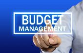 picture of budget  - Business concept image of a businessman clicking Budget Management button on virtual screen over blue background - JPG