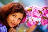 foto of lilas  - Young woman smelling a beautiful sakura blossom purple flowers - JPG