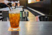 picture of iced-tea  - Glass of iced lemon tea on dark brown table in the restaurant - JPG