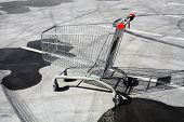 picture of trolley  - Color image of an abandoned shopping trolley in a parking lot - JPG