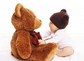 image of baby bear  - Baby in knitted brown hat playing with big teddy bear - JPG