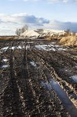 stock photo of boggy  - Mud and puddles on the dirt road with sand hills in the background - JPG