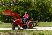stock photo of plowing  - A older farmer plowing his garden with a compact 4x4 tractor - JPG