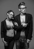 picture of tuxedo  - Young fashionable couple in glasses and tuxedos posing in the studio - JPG