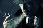 pic of mobsters  - Close up face of tired old crime lord smoking a cigarette and drinking a glass of wine in the dark  - JPG