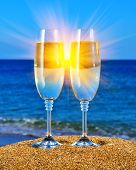 foto of champagne glasses  - Two glasses with champagne on the beach against the sunset - JPG