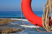 stock photo of coast guard  - Lifebuoy and rope close-up on a background of the rocky coast. horizontal
