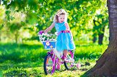 foto of little young child children girl toddler  - Happy child riding a bike - JPG