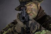 stock photo of m16  - Soldier in camouflage and modern weapon M4 on black background - JPG