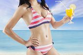 stock photo of swimsuit model  - Attractive female model wearing sexy swimsuit on the coast while holding a fresh drink - JPG