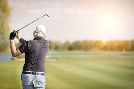 picture of swing  - Close up of male senior golf player swinging golf club - JPG