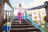 Little Girl Standing On Suspension Bridge On Playground, Hands On Rails