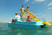 Happy Family With Boy And Girl On Pedal Boat With Yellow Slide In Sea, View From Water