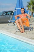 Young Woman In Orange Bikini And Pareo Sitting On Beach Chair