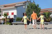 Little Boy And Two Girls Walking On Beach, Holding For Hands, View From Back, Trees And Building