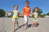 Little Boy And Two Girls Walking On Beach, Holding For Hands