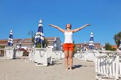 Young Woman In White Shirt Standing On Beach Near Lounges And Umbrellas, Hands Apart, Eyes Closed