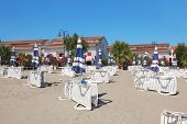 Many Lounges And Umbrellas On Beach Near Palms And Houses, Sunny Day