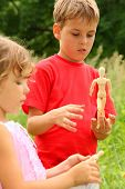 Little Brother And Sister Play With Wooden Little Manikins In Nature. Focus On Boy