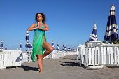 Beautiful Young Woman In Blue Swimsuit And Pareo Stands On Beach, Rows Of White Deck Chairs