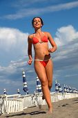 Beautiful Young Woman In Bathing Suit Runs On Sand On Beach, Rows Of White Loungers