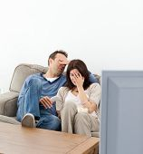 Scared Couple Hiding Their Faces While Watching A Horror Movie