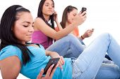 stock photo of mobile-phone  - three young girls texting on their cell phones isolated white background - JPG
