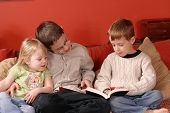 stock photo of storytime  - interior shot of 3 children reading a book - JPG