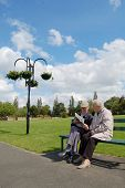 Senior couple on park bench reading newspaper