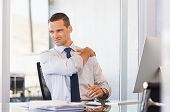 Young businessman at work suffering from shoulder pain. Businessman holding shoulder and stretching  poster