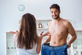 Man in oversized pants in weight loss concept with girlfriend wi poster