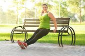 Overweight young woman exercising in park. Weight loss concept poster