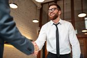 Close up of two young businessmen shaking hands to make a deal indoors poster