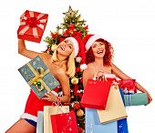 Christmas friends women with shopping bag and gift box having fun together under Xmas tree isolated. poster