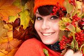Girl in autumn orange hat on leaf group. Outdoor.