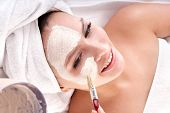 Cosmetician make mask to girl in spa. Facial massage.