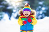 Child Playing With Snow In Winter. Kids Outdoors. poster