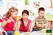 Children preschooler  with teacher draw paints in play room. Child care.