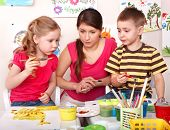 Children with teacher painting  paints in play room. Child care.