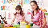 Little girl painting with teacher in preschool.