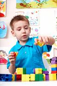 Little boy playing construction set .