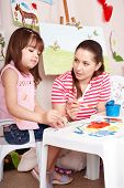Little girl playing with teacher in preschool.