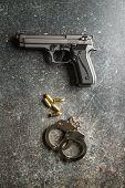 Pistol bullets, handgun and handcuffs on black table. poster